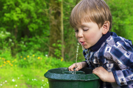 cute little boy drinking from a fountain Stock Photo