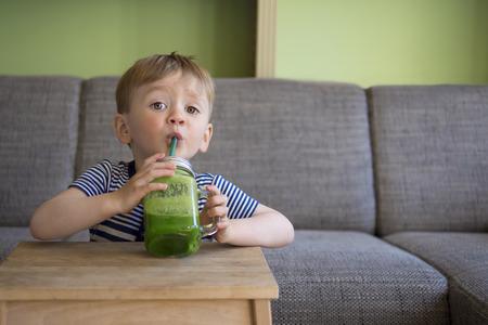 乳幼児: 緑のスムージーを飲む愛らしい幼児