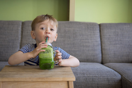 healthy people: adorable toddler drinking a green smoothie