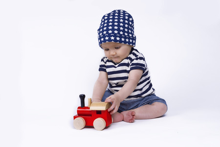 baby sitting: cute baby playing with a red train