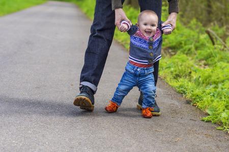 niños riendose: Padre guiar a su bebé con los primeros pasos