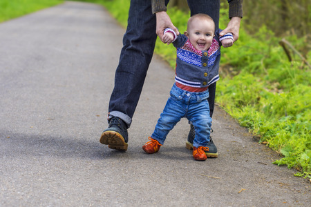 Father guiding his baby with the first steps