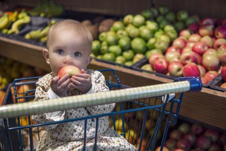 niños de compras: Lindo bebé en un carrito de la compra que come una manzana