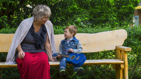 babysit: Grandmother and grandson singing and playing in a park Stock Photo