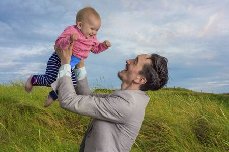 air baby: Father holding his baby daughter high in the air