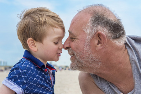 fun: Grandfather and grandson having fun on the beach Stock Photo