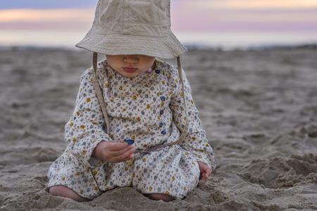 乳幼児: ビーチで貝殻で遊ぶかわいい赤ちゃん女の子 写真素材