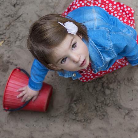 ojos marrones: hermosa niña con los ojos marrones en la caja de arena