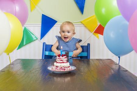 축하: 그녀의 첫 번째 생일 촛불을 불고 슈퍼 귀여운 아기 스톡 콘텐츠