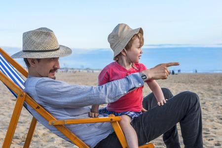 bebe sentado: Padre de pasar un día en la playa con su hijo Foto de archivo