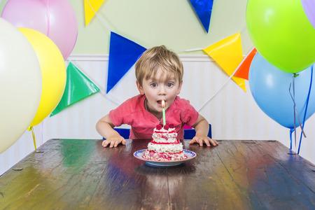 velas de cumpleaños: Cabrito adorable que sopla la vela de su pastel de cumpleaños Foto de archivo
