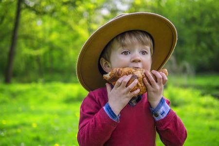 comiendo pan: Adorable niño morder en un croissant Foto de archivo