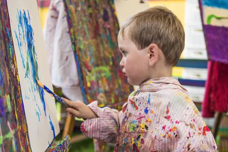 making: Cute little preschooler making a painting in art class