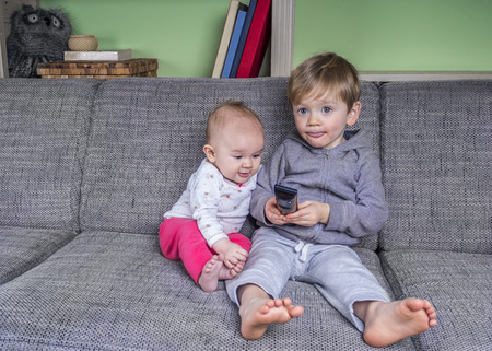 tv remote: Two small children watching television on the couch