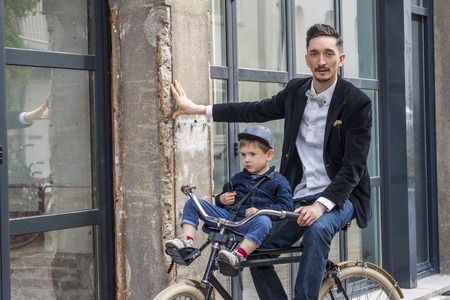 old school bike: Father and son riding the bicycle in the city Stock Photo