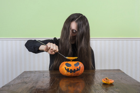 ghost face: Scary ghost lady eating pumpkin soup