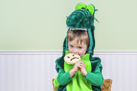Adorable little boy in a crocodile suit eats a Halloween cookie Stock Photo