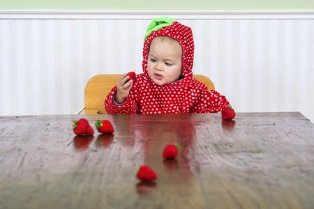 cute baby in berry suit eating strawberries Banco de Imagens