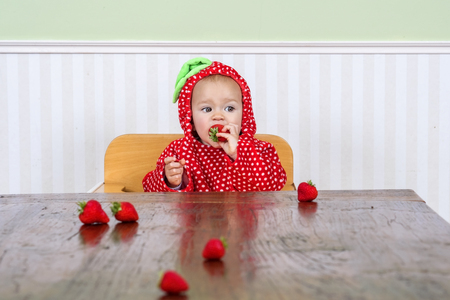 Adorable baby in a berry suit eating strawberries