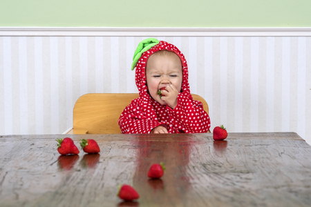Cheerful baby in strawberry suit eating strawberries