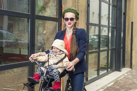 urban parenting: Trendy mother and daughter riding a bicycle in the city