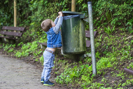 soil pollution: Little child throwing trash in the bin Stock Photo