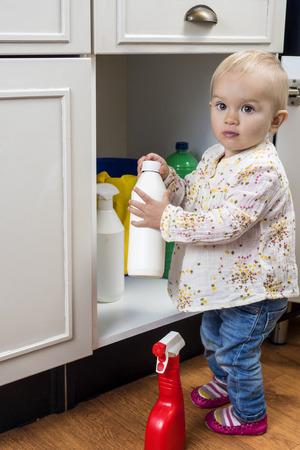 riesgo quimico: Pequeño niño que juega con los productos de limpieza en el hogar Foto de archivo