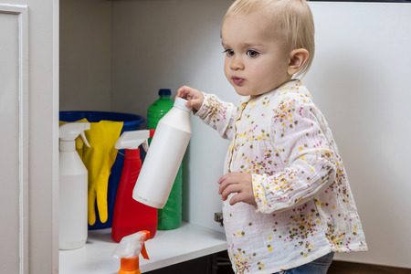 safety first: Toddler playing with household cleaners at home Stock Photo