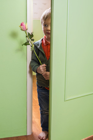 wake up happy: Adorable little boy holding a pink rose