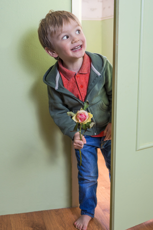 Cheerful little boy holding a rose