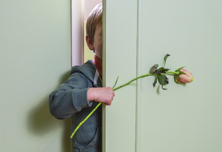little kid hiding behind the door and holding a flower