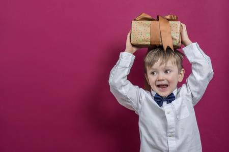 その快活な少年がプレゼントを開催します。 写真素材