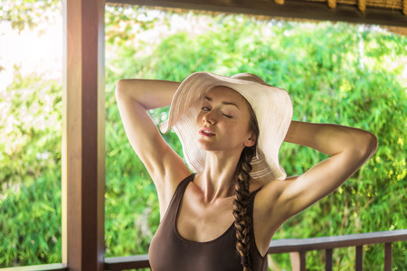 Young lady relaxing in the morning sun on her balcony Stock Photo