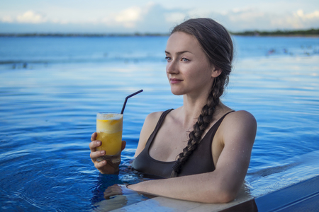 Young woman enjoying a drink in the pool at sunset