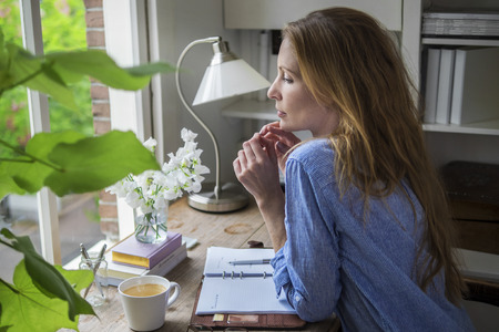 Attractive lady drinking morning coffee in her home office Stock fotó