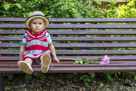 Cute sitting on a bench toddler looking grumpy Stock Photo