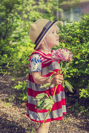 Beautiful little girl holding a flower in the garden