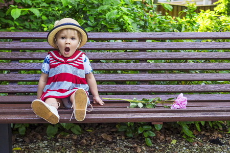stood up: Cute little girl yawning while sitting on the bench Stock Photo
