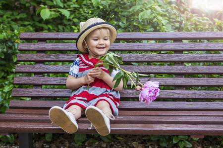 Cute little girl sitting on a bench with a flower Stock Photo