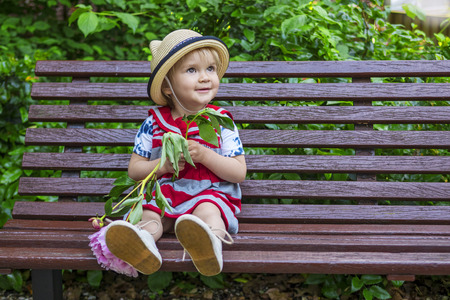 beautiful toddler girl sitting on a bench holding a flower photo
