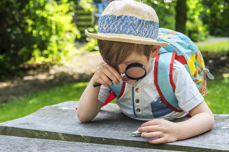Little boy looking through magnifying glass Stock Photo