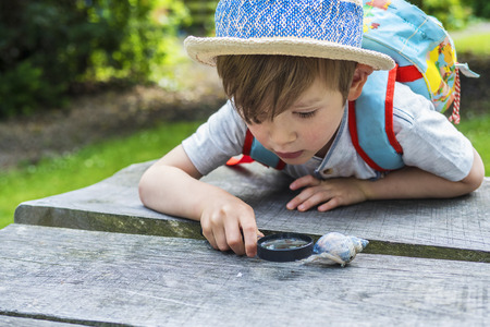 discovering: Little discovering nature through a magnifying glass