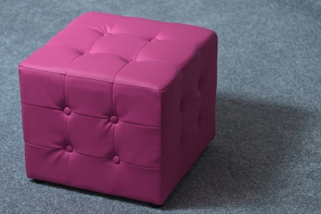 Leather pink footstool isolated on grey carpet