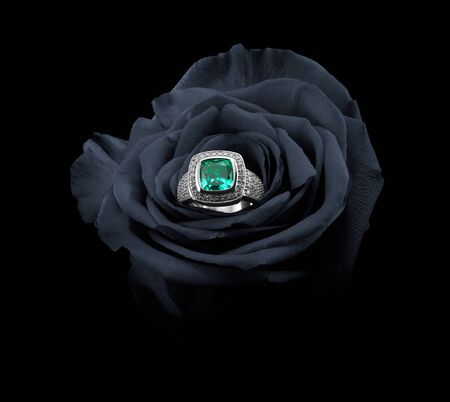 rose ring: Rose on a black background with emerald ring inside Stock Photo