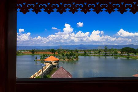 The triangular pavilion is situated in the middle of the water, with long corridors, white clouds, lush mountains and a beautiful blue sky as the backdrop.