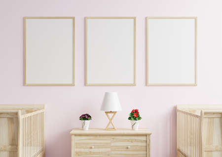 Picture frame on the pink wall in the child's bedroom. There was a newborn bed on the side and a lamp and flower pot placed on the wooden cabinet.3d rendering