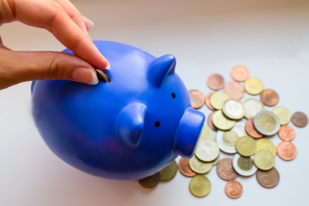 Hand put coin in blue piggy moneybox, which stay on other coins Stock Photo
