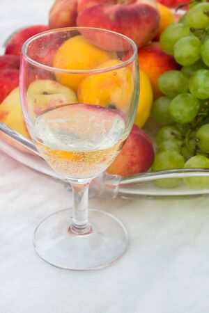 Glass of white wine and plate with grapes and peaches  Stock Photo