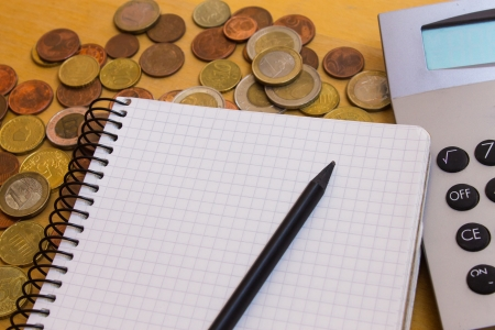 Money near calculator and white notebook with black pencil