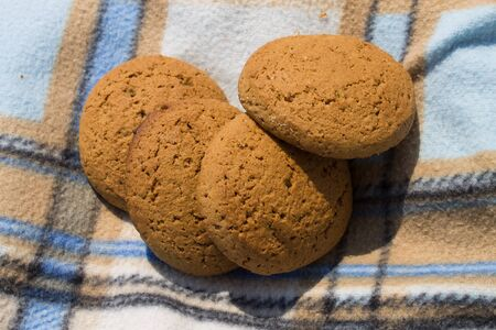 Homemade oatcake, brown cookies on checkered background